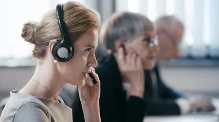 телемаркетинг : selective focus of attractive woman in headset talking while consulting and smiling near coworkers