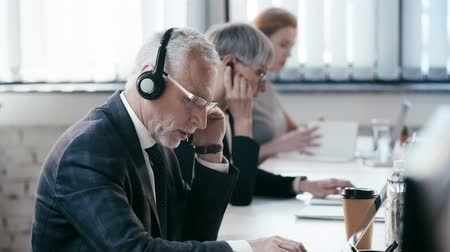 телемаркетинг : selective focus of bearded man in headset talking and typing on laptop near businesswomen in office