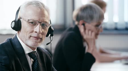 телемаркетинг : selective focus of teleworker in headset talking near coworkers, smiling and looking at camera