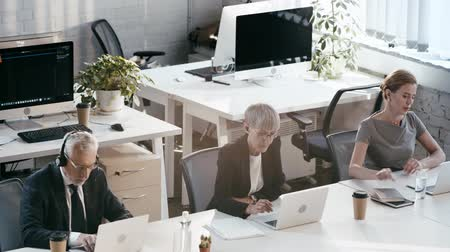телемаркетинг : overhead view of businessman and businesswoman taking notebooks, woman drinking water while working in office