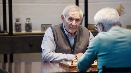 šachy : two pensive senior men talking while playing chess at table in living room