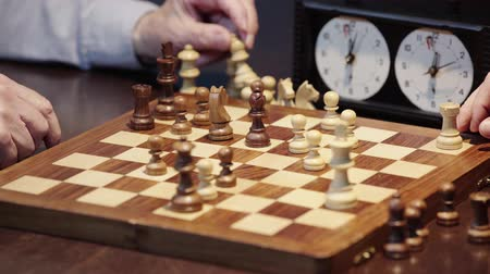 tabuleiro de xadrez : partial view of two senior men gesturing while playing chess at table Stock Footage