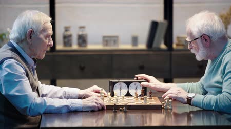 presleme : side view of two pensive senior men playing chess and pressing button on chess clock at table Stok Video