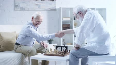 opponent : happy senior man sitting near chessboard, shaking hands with opponent and laughing in living room