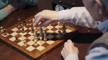 presleme : partial view of two senior men playing chess and pressing button on chess clock at wooden table Stok Video