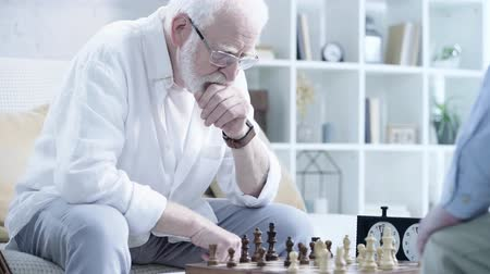 načasování : pensive bearded man in glasses playing chess with opponent and pressing button on chess clock