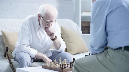 presleme : cropped view of two pensive senior men playing chess and pressing button on chess clock