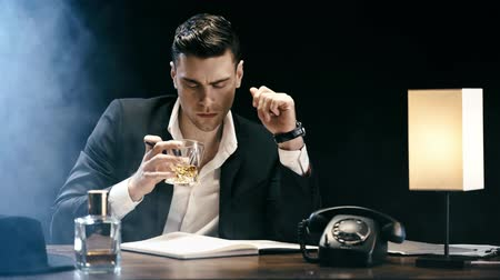 telephone handset : focused businessman writing in textbook and drinking whiskey while sitting at table on black