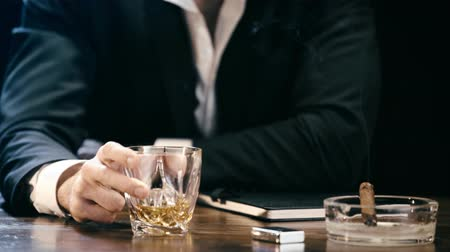 zapalovač : cropped view of businessman sitting at wooden table with cigar in ashtray and shaking glass of whiskey