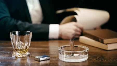 briquet : partial view of businessman sitting at table with cigar and ashtray, lighter and glass of whiskey and holding papers