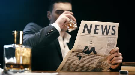 газета : selective focus of businessman reading newspaper and drinking whiskey at table on black
