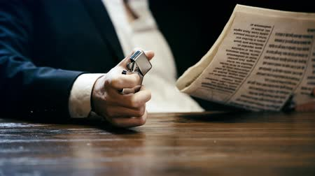 jornal : cropped view of businessman sitting at wooden table, reading newspaper and holding lighter Vídeos