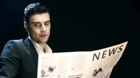 газета : focused businessman reading newspaper, blinking and looking at camera with smile on black
