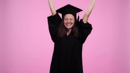 mortarboard : happy student in academic gown cheering with clenched hands and showing diploma at camera Isolated On pink
