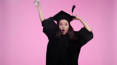 mortarboard : excited student in academic gown looking at camera and jumping with graduation cap and diploma Isolated On pink