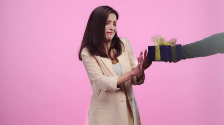 ontevreden : dissatisfied girl refusing gift box from man then taking gift from woman, smiling and looking at camera On pink