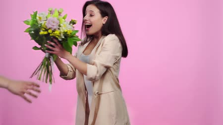 cheirando : man giving bouquet to excited girl, girl sniffing flowers and looking at camera Isolated On pink