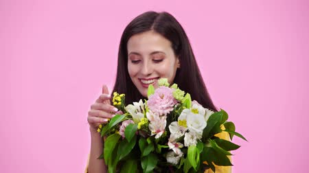 cheirando : beautiful girl sniffing flowers, looking at camera and smiling Isolated On pink