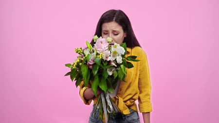 cheirando : smiling girl sniffing flowers, sneezing and looking at camera Isolated On pink