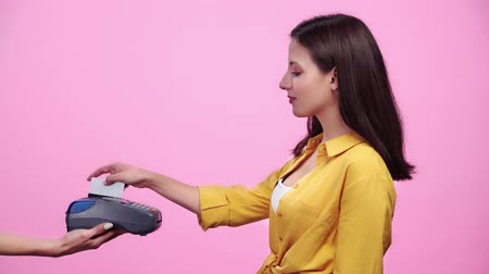 lezer : woman holding payment terminal while happy girl paying with credit card Isolated On pink Stockvideo