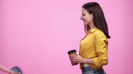 payment terminal : woman giving coffee to go to girl then holding payment terminal while happy girl paying with credit card Isolated On pink