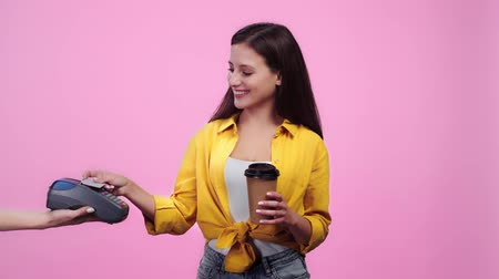 payment terminal : woman holding payment terminal while happy girl paying with credit card and then drinking coffee to go Isolated On pink
