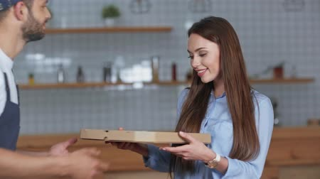 delivery man giving pizza box to happy woman at home