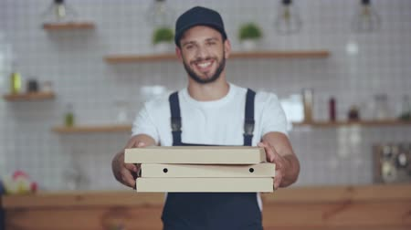 focus pull : rack focus of cheerful bearded delivery man holding boxes and looking at camera