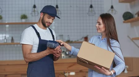 happy girl taking carton box and woman paying by smartphone while delivery man holding credit card reader