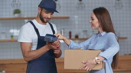 fattorino : delivery man holding credit card reader and carton box and woman paying by credit card at home