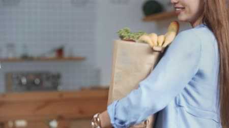 focus pull : Focus pull of delivery man holding paper bag with groceries and cheerful giving to girl at home