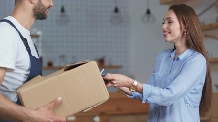 handsome delivery man giving clipboard to girl, young woman signing and receiving box and waving hand at home