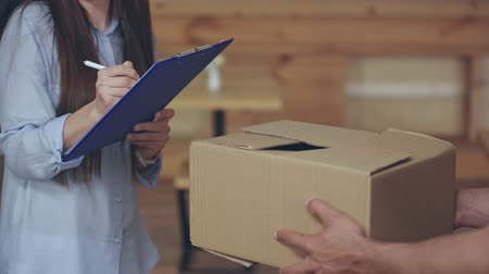 focus pull : rack focus of delivery man giving clipboard, girl signing and taking carton box at home Stock Footage