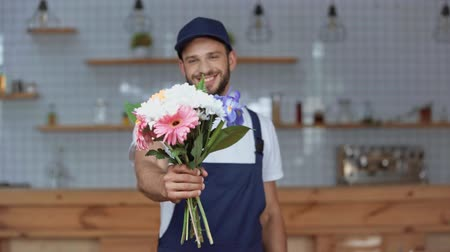 focus pull : Focus pull of handsome delivery man looking at camera, smiling and holding flowers