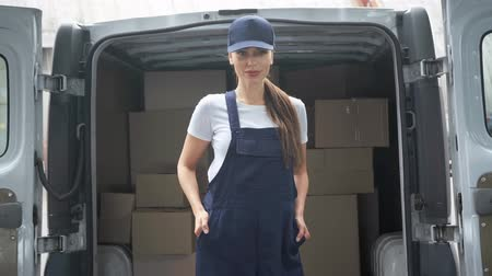 samochód : attractive delivery woman in cap and uniform standing with hands in pockets and smiling near car with packages