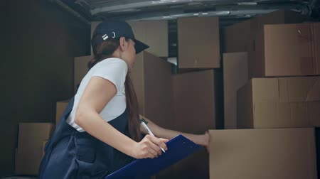 happy delivery woman in cap writing while holding clipboard, touching boxes and looking at camera