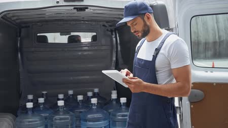 hidratáció : handsome bearded man in cap using digital tablet while standing near car with bottles of water