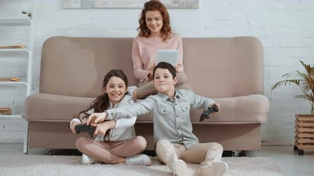 front view of smiling children with joysticks playing video game while mother sitting on sofa and using digital tablet
