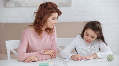 smiling mother helping daughter with homework while she writing in copy book at desk