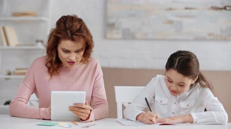 schoolkid : beautiful smiling mother using digital tablet at desk while daughter doing homework Stock Footage
