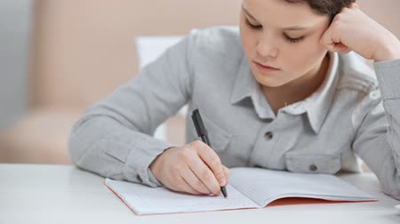 boyhood : focused preteen schoolboy propping face with hand while writing in copy book at desk Stock Footage