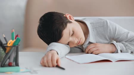 tired preteen schoolboy with pen sleeping on desk near copy book, calculator and pencils Stok Video