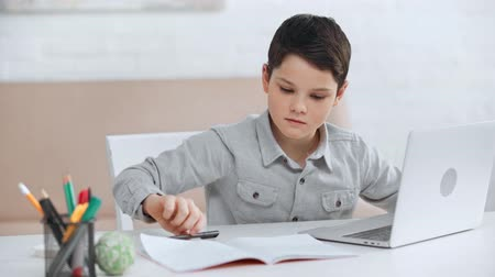focused preteen schoolboy using laptop and writing in copy book while doing homework at desk