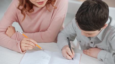 домашнее задание : mother holding pencil and helping son with homework while he writing on copy book at desk