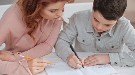 boyhood : mother holding pencil and helping son with homework while he writing on copy book at desk