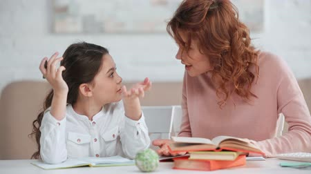 quarreling : annoyed mother and daughter arguing while doing homework at desk Stock Footage