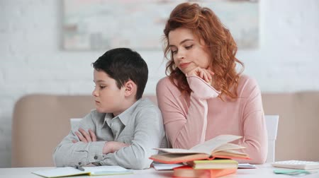 offended preteen boy sitting with crossed arms and looking at mother at desk with books