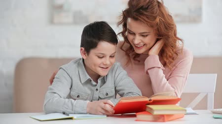 boyhood : smiling mother helping son with homework while he reading book at desk Stock Footage
