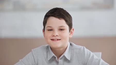 front view of smiling preteen boy blinking while looking at camera