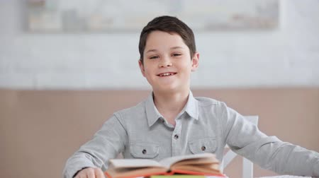 front view of smiling preteen boy sitting at desk, showing thumbs up and rock signs, making funny faces and putting book on head